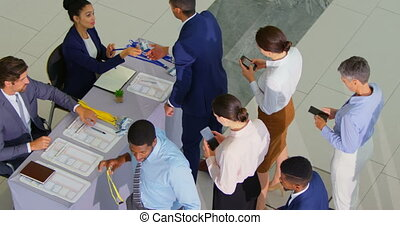 Business people checking in at conference registration table...