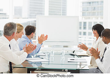 Business people clapping at blank w