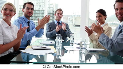Business people clapping at camera in board room in the...