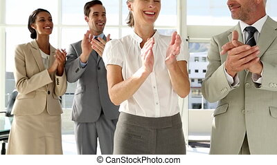 Business people clapping at the camera in office with large...