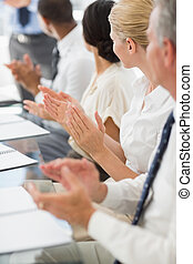 Business people clapping colleague at a meeting in the...