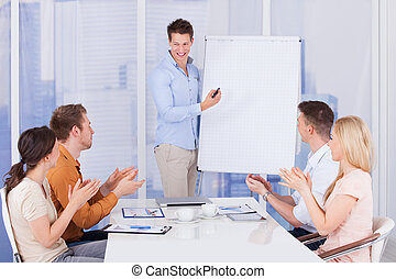 Business People Clapping For Colleague After Presentation
