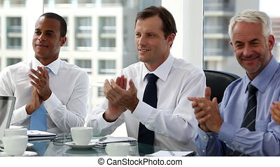 Business people clapping sitting in board room after presentation