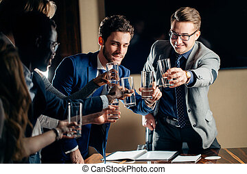business people clinking glasses and smiling while celebrating in meeting