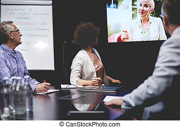 Business people communicating by television set