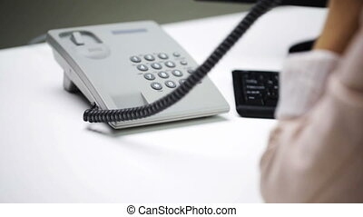 woman hand dialing number on telephone at office - business,...