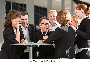 Business people congratulating coworker