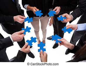 Business people connecting puzzle pieces over white ...