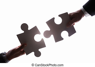 Business people connecting two jigzaw puzzle pieces
