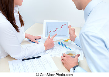 Business people discussing about the success sales and using...