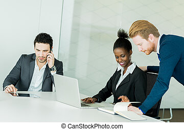 Business people discussing and brainstorming at a white desk in an office