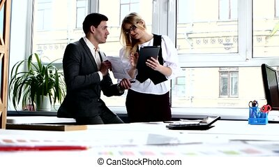 Business people discussing business issues: blonde with glasses explain something to a colleague on the tablet.