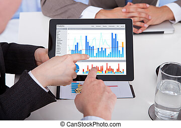 Business People Discussing Graph On Digital Tablet In Office