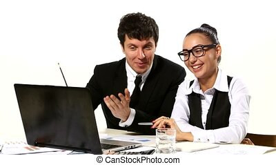 Business people discussing ideas looking at laptop, gesturing vividly. The smiles on their faces