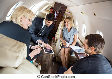 Business People Discussing In Corporate Jet - Businessman...