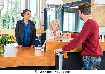 Business People Discussing In Modern Office Lobby