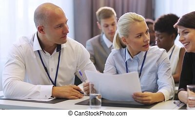 business people discussing papers at conference - business,...