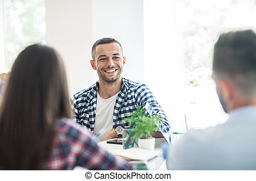 Business people discussing project at meeting in modern office