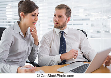 Business people discussing something on laptop
