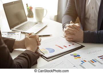 Business people discussing the charts and graphs showing the results of their successful teamwork at office