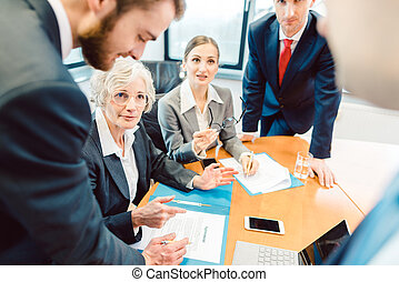 Business people during negotiation of an agreement discussing