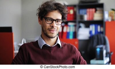 smiling young man in eyeglasses at office - business,...