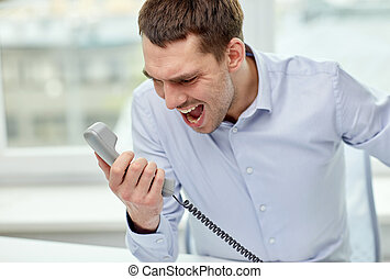 furious businessman calling on phone in office