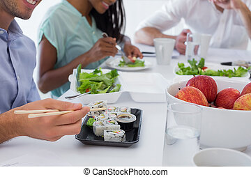 Business people enjoying sushi and