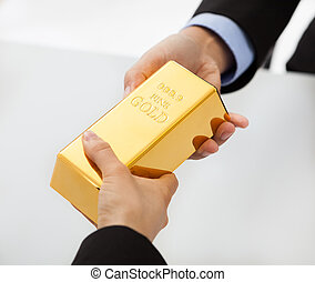 Business people exchanging golden bar - Close-up on hand of...
