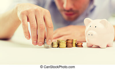 close up of businessman with piggy bank and coins