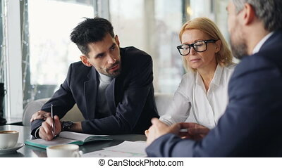 Business people focused on discussion talking in cafe...