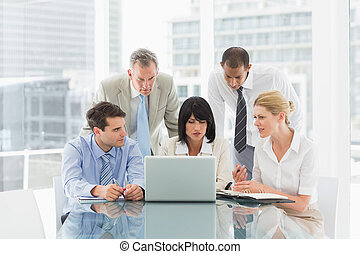 Business people gathered around laptop talking in the office