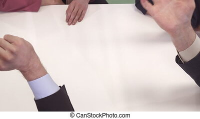 Business people gesture at the table