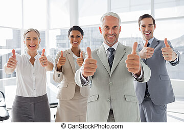 Business people giving thumbs up in the meeting room