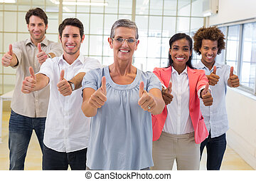 Business people giving thumbs up to camera and smiling in...