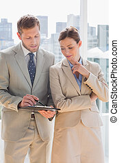 Business people going over document on clipboard