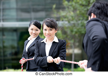 Business people having a tug of war fight. - Asian...