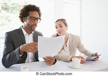 Business people having coffee looking at file