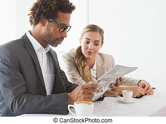 Business people having coffee looking at newspaper