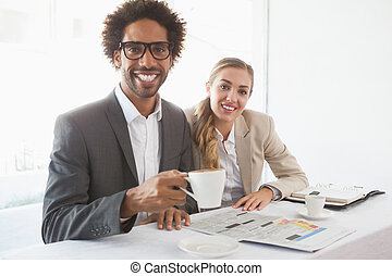 Business people having coffee smiling at camera