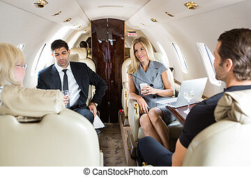 Business People Having Drinks On Private Jet