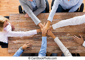 business people holding hands at office table - business,...