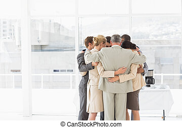 Business people hugging in a circle