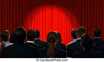 Business people in a theatre watching encouraging words - ...