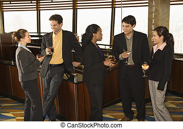Business people in bar. - Ethnically diverse group of...