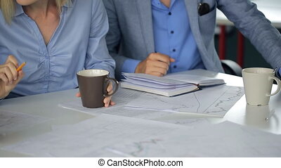 Business people in blue shirts sit at table in office in day time.