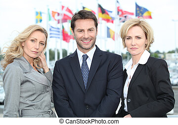 Business people in front of flags