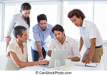 Business people interacting and looking at laptop in the...