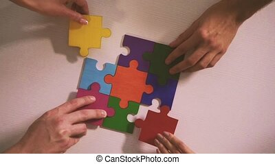 Business people join puzzle pieces in office. Concept of...