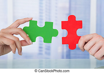Business People Joining Jigsaw Pieces In Office - Cropped...